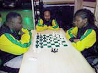 Appearing resplendent in their famous sports uniform is Jamaica's chess contingent for the 2014 Umada Cup. National Master Andrew Mellace (2083) is concentrating deeply during a friendly game against Woman International Master Deborah Richards-Porter (2013) at the Regency Hotel on Hadfield St. At the centre of the photo taking an interest in the game is Candidate Master Ras Malaku Lorne (2084). The three Jamaican chess players arrived in Guyana on Wednesday for the celebrated Umada Cup which is being held locally for the first time.