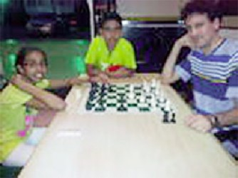 Two kids from Suriname, Alisha Jai Persaud, 11, and Ishvar Ramlal,12,  and a male chess player from Barbados, Fide Master Martyn Del Castillo pause from a warm-up encounter to allow a photo to be taken on Wednesday afternoon at the Regency Hotel. The trio is here to participate in the Umada Cup five-day tournament. Del Castillo had emerged victorious in the 2011 version of the Umada Cup.