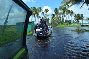 Media personnel hitch a ride on the tray of a police vehicle as they survey the damage done to the Manzanilla-Mayaro Road yesterday following floods at the weekend.