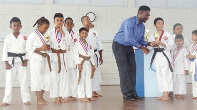 Sports Coordinator of the Marian Academy Chris Bowman handing over a trophy to Karateka Zachary Persaud