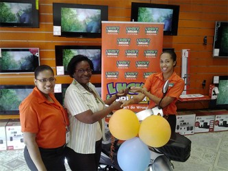 This Lucky Dollar photo shows Denise Benjamin (centre) receiving her prize