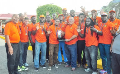 The jubilant national rugby squad and now seven-time NACRA champions pose with the coveted trophy shortly after arriving at the Cheddi Jagan International Airport, Timehri yesterday. (Orlando Charles photo)