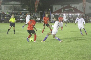 Alpha United's Travis Grant (no.8) trying to maintain possession of the ball while being challenged by a Black Water player during the opening match of the GFA/Banks Beer Cup
