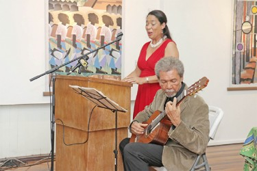 Ena Harvey sings while Stanley Greaves plays the guitar at the launch of his exhibition