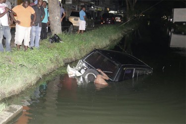 The sunken RAV 4 being connected to a tow truck cable by a volunteer last evening, to be removed from the South Road trench.