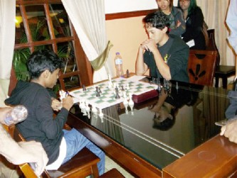 """Teenage Surinamese chess player Geryen Dos Ramos (right) and Trinidad and Tobago's Mikel Martin,13, contested a furious middle-game battle during their Round 9 encounter at the 2014 Guyana Umada Chess Cup. It was the last game of the tournament to be completed before the prize-giving ceremony, and, therefore, it commanded the attention of the entire tournament hall. Geryen was calm, since he possessed a connected passed pawn. Mikel temporarily blocked the pawn with a Rook, thereby tying-up a major piece in the process. With his remaining pieces however, Mikel launched a sudden and vigorous attack on Geryen's king, proceeding to deliver some thunderbolts against his steadfast opponent. Mikel's mom, a chess player herself, was photographing the different moods of her son as he was launching his attack. """"Mikel can draw that position,""""  Mom said to no one in particular. """"Yes, it's a draw,"""" she reasoned. But Mikel was in time trouble. And time trouble could be suicidal when you are attacking. He was forced to play quickly, eventually losing some more pawns and ultimately losing the game. Afterwards, Mom was tender in her assessment of the game on behalf of Mikel: """"You know, he's only 13; he has a long way yet to go,"""" she said. Geryen is the son of Dr Richard Dos Ramos, who played chess in Guyana in the 1970s and '80s, along with his brother Carlos. We still remember the game when Gordon Broomes checkmated Richard with two Bishops, as he (Gordon) was experiencing severe time trouble!"""