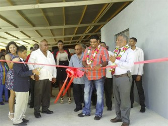 Minister of Tourism, Industry and Commerce, Irfaan Ali (second from right) and David Safeek( second from left) cut the ribbon as the Prime Minister, Samuel Hinds (front right) and other guests looks on.