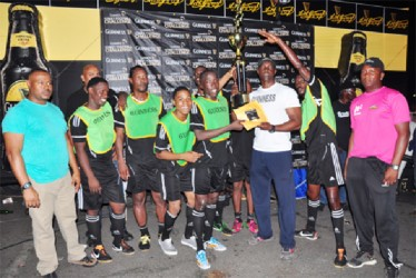 North Georgetown's Joshua Browne collects the championship trophy and first prize from Banks DIH Limited Guinness Brand Manager Lee Baptiste as members of the winning team and Banks DIH officials look on. (Orlando Charles photo)