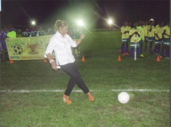 Dr Jennifer Westford performs the ceremonial kick off to declare this year's Upper Demerara Football Association/Banks GT Beer Cup football tournament open.