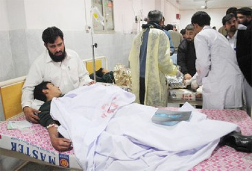 A man comforts his son, who was injured during an attack by Taliban gunmen on the Army Public School, at Lady Reading Hospital in Peshawar, December 16, 2014. REUTERS/Stringer