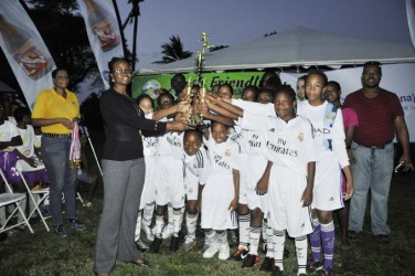 Stella Maris Primary receiving their championship trophy from Ministry of Health Representative Dr. Ertenisa Hamilton following the conclusion of the event's finale