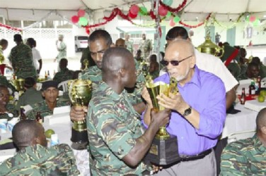 "President Donald Ramotar (right) being offered a sip from the ""Trophy"" by a rank of the Guyana Defence Force (GINA photo)"