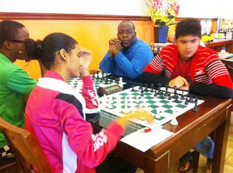 Suriname's Woman Candidate Master Reyna Frijde faces Guyanese Roberto Neto at the start of their round six encounter at the 2014 Guyana Umada Chess Cup. Playing the advantageous white pieces, Reyna out-manoeuvred her opponent to seize the full point. Sitting next to Roberto is Candidate Master Ronuel Greenidge who represented Guyana diligently at the 2014Tromso Chess Olympiad in Norway. Ronuel's opponent is Wendell Muesa who contested the tournament under the Barbadian flag.