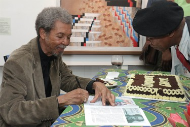 Stanley Greaves signing exhibition catalogues at the end of the birthday celebration in his  honour hosted by the National Gallery of Art at Castellani House (Photo by Arian Browne)