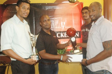 Ryan Gullen (right) of the victorious Pitbulls unit collecting the championship trophy and winner's cheque from Mackeson Brand Manager Jamal Douglas while teammates Jermin Slater (left) and Akeem Kanhai look on.
