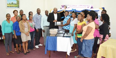 Chief Executive Officer of Southern Systems Karl Moore (tenth, left) hands over the donation in the presence of library staff and Thompson's family.