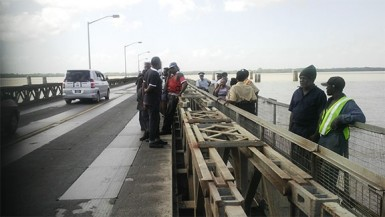 Police officers and Demerara Harbour Bridge Corporation officials standing at the spot where the unidentified woman jumped to her death yesterday, off the Demerara Harbour Bridge.
