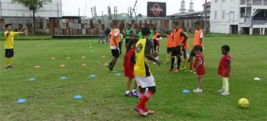 Members of the Georgetown Football Club (GFC) junior teams being put through the paces by team manager Faizal Khan (left) during a training session at the club's Bourda locale