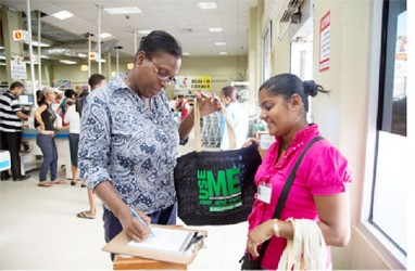 A shopper signing a pledge to use the bag (Guyenterprise photo)