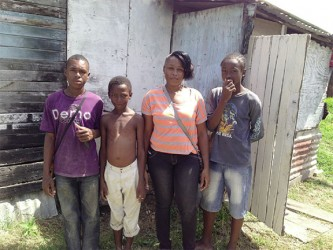 Corina with her sons and brother (at left) in front of her humble 'apartment'