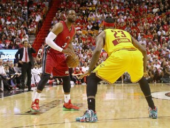 Dwyane Wade, with ball being challenged by former teammate LeBron James of the Cleveland Cavaliers in their Christmas Day matchup at American Airlines Arena which the Heat won with Wade scoring 31 points and James 30 for Cleveland.