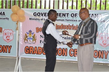 Minister in the Ministry of Finance, Juan Edghill presents a certificate to one of the Linden graduates (GINA photo)