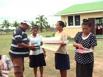 Frank Singh of Rainforest Tours presents educational materials to teachers in the South Rupununi (GINA photo)