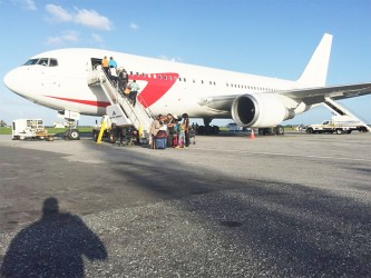 Have plane, will travel: Passengers boarding a Dynamic Airways flight at the Cheddi Jagan Inernational Airport earlier this week.