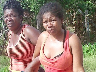 Pamela Gittens (right) being comforted by a friend