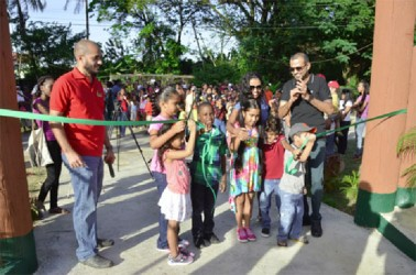 Damian Fernandes (left), Commissioner of the Protected Areas Commission and Minister of Natural Resources and the Environment Robert Persaud (right) observe the cutting of the ribbon at the commissioning of the Zoological Park's Petting Zoo yesterday. (See page 10)