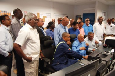 A young technician (seated, left) shows how the system works while President Donald Ramotar (seated, centre and Prime Minister Sam Hinds (right) look on. They are flanked by government and GPL officials.
