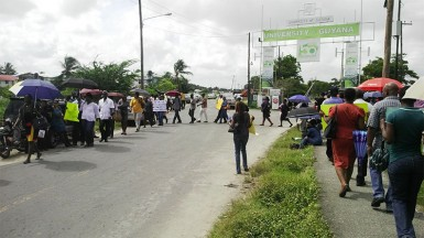 UG staff circling the entrance to the University of Guyana Turkeyen Campus yesterday at the start of a three-day strike.