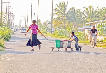 Benneta Kissoon and one of her boys fetching water from a kind-hearted neighbour to her home across the road along the Railway Embankment at Non Pareil, East Coast Demerara. (Photo by Arian Browne)