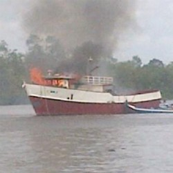 A small boat guiding the burning trawler
