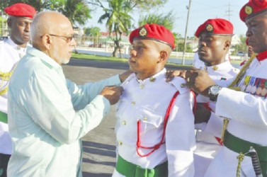 Commander- in-Chief, President Donald Ramotar (left) and Chief of Staff, Brigadier Mark Phillips pinning on the badge of rank of newly commissioned 99921 Second Lieutenant (2Lt) Lewins Langellier (GINA photo)