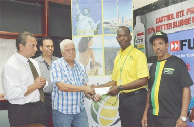 Wesley Tucker, Senior Marketing Officer of Fly Jamaica (right), hands over the two airline tickets to Michael Fung of the GBBC.