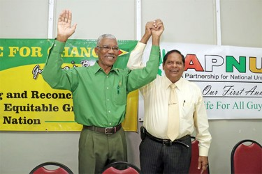 APNU's David Granger (left) and AFC's Moses Nagamootoo, presidential and prime ministerial candidates of the new coalition, raise joined hands after the announcement yesterday at the Georgetown Club, Camp Street. (Photo by Arian Browne)