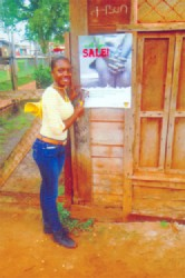 GWMO member Amanda Peters stands next to an anti-human trafficking poster she had just placed on a shop door in Mahdia.