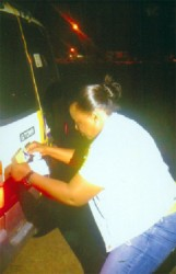 GWMO President Simona Broomes puts an anti-human trafficking sticker on a minibus at Mahdia.