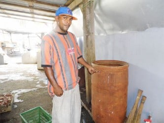 Anand Ramjass pointing to the new colour of his water barrel compliments of the water  supplied by GWI