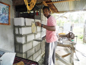 19-year-old Amarnauth Narassiah plastering a concrete wall he erected to extend his family home