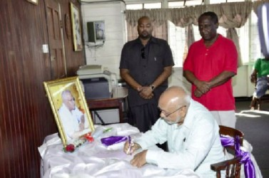 President Donald Ramotar signing the Book of Condolence for Leslie Melville at the Guyana Public Service Union, Shiv Chanderpaul Drive.  Standing at right is GPSU President Patrick Yarde. (GINA photo)