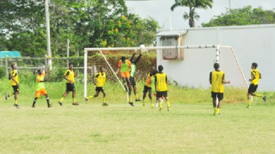 St. George's High's Adolph George (centre) attempting to latch onto a right sided cross while being challenged by the Brickdam Secondary goalkeeper during his side's comprehensive victory.