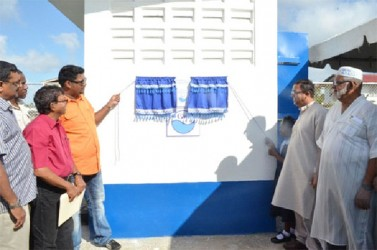 Minister of Housing and Water, Irfaan Ali (third from left) unveiling the plaque to commission the well at Manchester, Region Six. (GINA photo)