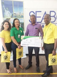 President of the GTTA, Godfrey Munroe smiling after receiving Fly Jamaica's sponsorship package from Marketing Manager, Nadine Hing.