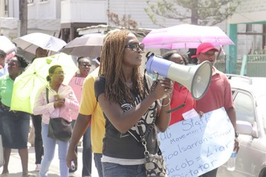Dr Mellissa Ifill leading the chant during yesterday's march to the city by striking university workers.