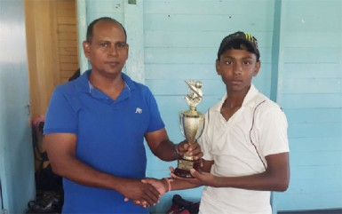 Kelvin Omroa receives his MVP trophy from Nazimul Drepaul, GCB Junior National Selector. (Orlando Charles photo)