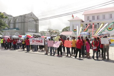 The University of Guyana staff members picketing opposite the Ministry of Education yesterday.