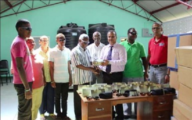 Food for the Poor Guyana Inc CEO Kent Vincent (at right) during the handing over of sunglasses to President of the Society for the Blind Cecil Morris.