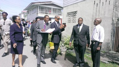 Donald Rodney (right) stands beside his lawyer Keith Scotland as he showed the Chairman of the Commission of Inquiry Sir Richard Cheltenham (second left) and Commissioner Jacqueline Samuels-Brown (left) where his car was parked while he went to Gregory Smith's house in Russell Street.